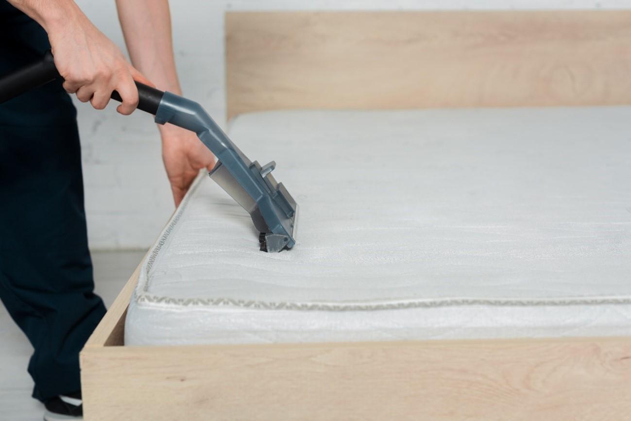 Persona limpiando con una vaporeta un colchón de gomaespuma